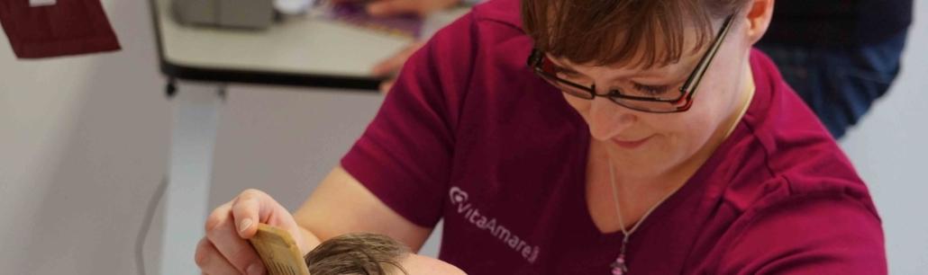 Symbolbild Intensivpflege VitaConSana: Frau sieht auf Patient und kämmt ihn