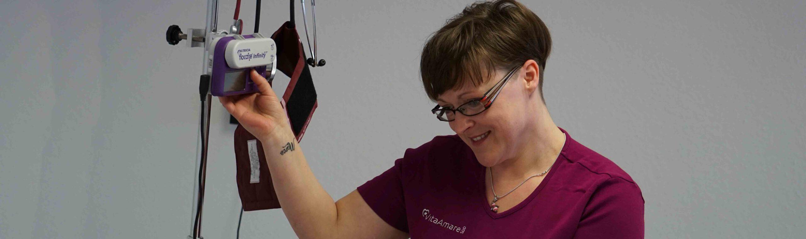 Frau schaut auf Patienten und nutzt Medizintechnik bei Intensivpflege VitaConSana