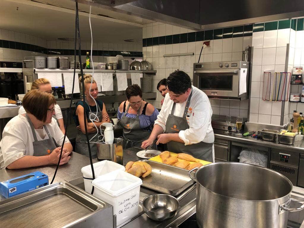 Frauen und Männer in einer Gastronomie-Küche beim Kochkurs zeigen Teamerlebnis Pflegefachkraft bei VitaConSana